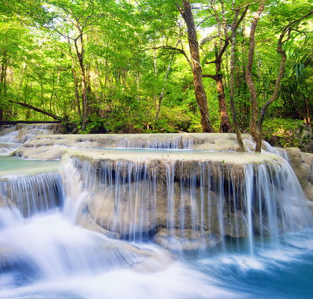 Waterfall landscape background  Beautiful nature outdoor photography  Thailand green rain forest jungle with trees and bushes, fresh clean and cool water river flows through stones cascades and roots photo