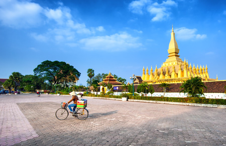 vientiane: VIENTIANE, LAOS - 11 DEC,2013: Unidentified local woman on the bicycle on the square near golden pagoda wat Phra That Luang in Vientiane. Popular travel destination Editorial