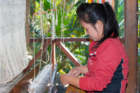 LUANG PRABANG, LAOS - 8 DEC, 2013: Unidentified female worker in silk production factory. Traditional way of making textile is very popular tourist attraction. Showrooms and masterclasses take place