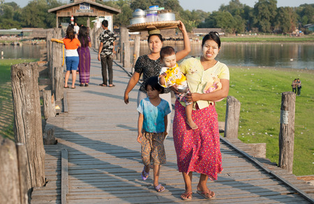 believed: MANDALAY, MYANMAR - JAN 19, 2014  Unidentified local citizens of Amarapura crossing U Bein bridge located on Taungthaman Lake  Bridge is believed to be the oldest and longest teak bridge in the world