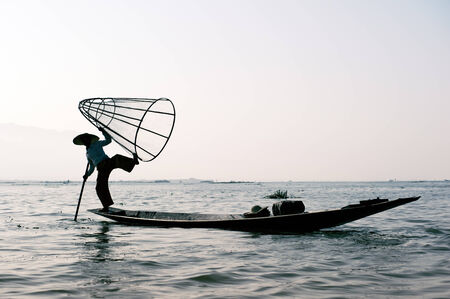 Traveling to Myanmar, outdoor photography of fisherman on traditional boat  Intha people from Shan state of Burma photo