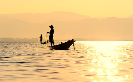 Traveling to Myanmar, outdoor photography of fisherman on traditional boat. Intha people from Shan state of Burma photo