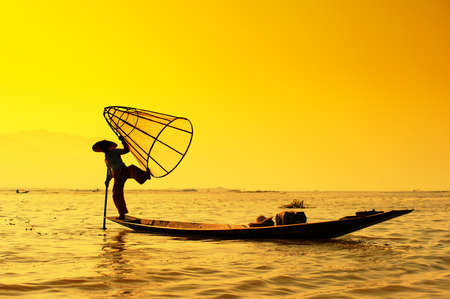 Myanmar, Shan state, Inle lake Intha fisherman on boat at amazing sunset photo