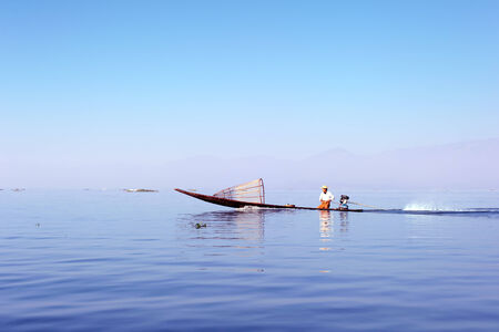 Myanmar, Shan state, Inle lake Intha fisherman on boat at early sunrise photo