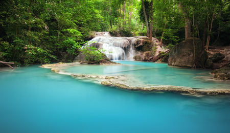 Green forest and mountain river with waterfall cascades in tropical jungle environment of Thailand
