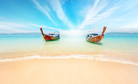 Thailand nature landscape. Sandy beach and travel boats on coast of tropical island near Phuket