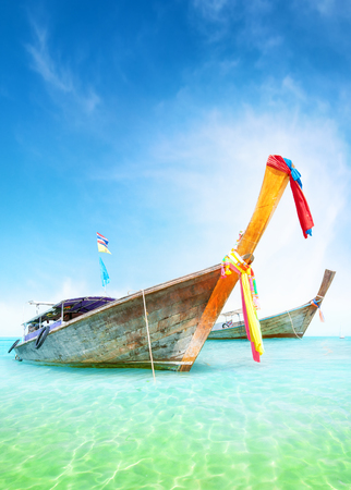 shore: Vacation journey summer background. Traditional thai boats on turquoise water of tropical sea shore Stock Photo