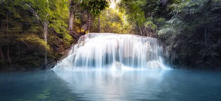 Cool fresh water pond in forest with smooth and silky waterfall cascades. Nature background panorama