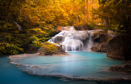 Orange autumn leaves of wild dense forest and scenic waterfall falls in natural blue water pond