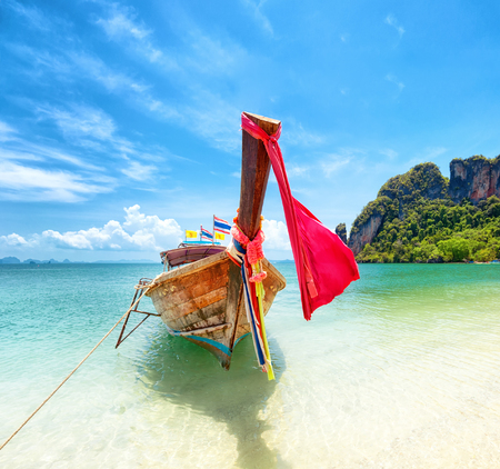 Tourism in Asia. Tropical island and tourist boat on exotic sandy beach in Thailand. Travel background
