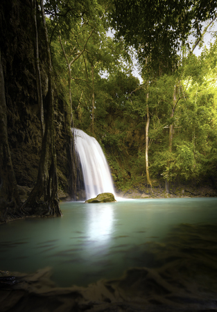Vertical nature background of tropical waterfall in jungle forest with warm sunlight shines through trees and leaves Zdjęcie Seryjne