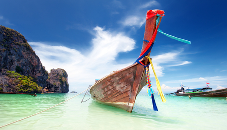 Adventure landscape background. Wooden fishing boat on sea coast of tropical island in Thailand at sunny day of summer vacations in Asia