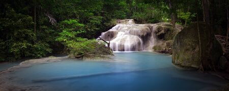 Pond with clear blue water and waterfall in Thailand rainforest. Panoramic nature background