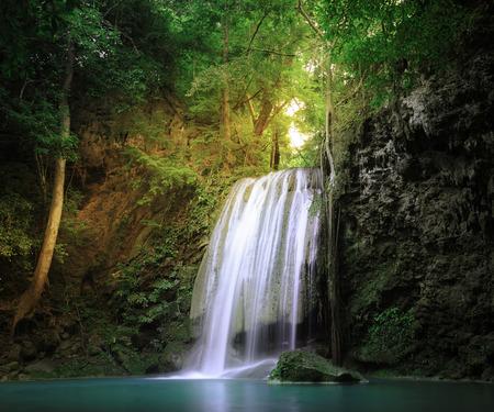 Prachtige natuur plaats. Zonlicht balken en stralen schijnt door wilde jungle bos bomen en bladeren van de planten rond rustige waterval vallen in natuurlijke vijver