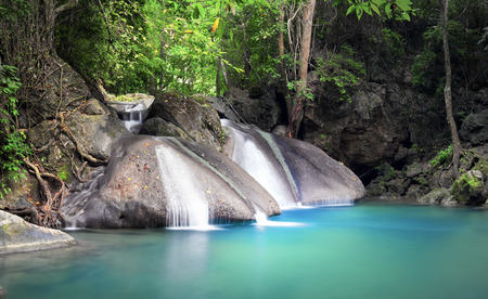 Peaceful and relaxing landscape background of tropical forest with small beautiful waterfall flowing from wet stones and rocks and falling in blue water lake