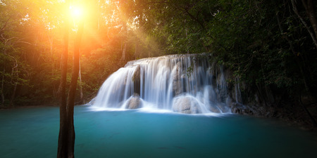 cascade: Sunlight in forest with waterfall Stock Photo