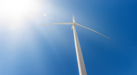 Power generating wind turbine on blue sky with bright sun rays