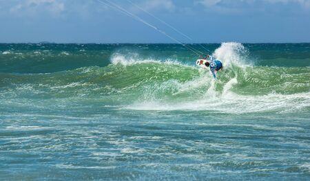 kiteboarding: Summer sport water activity background - male kite surfer on high wave