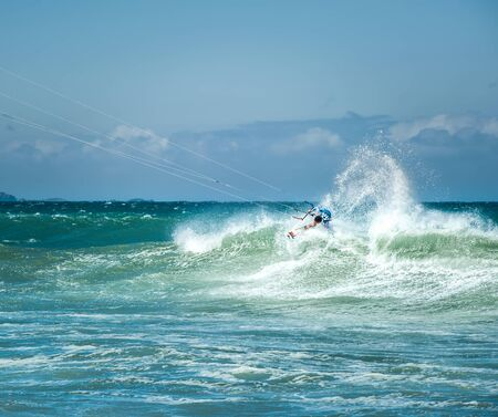 kiteboarding: Kitesurfer sportsman makes acrobatic trick on big sea wave Stock Photo