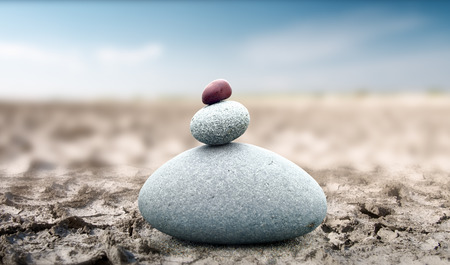 Spiritual and peaceful rock pebble tower on dry deserted land. Zen like conceptual background 版權商用圖片