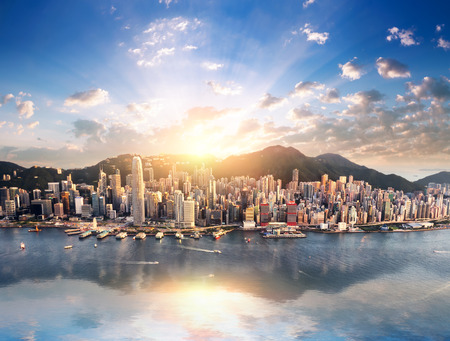 cenital: Hong Kong horizonte de la ciudad vista desde el puerto con edificios rascacielos refleja en el agua al atardecer con la luz del sol y los rayos del sol brillando a través de nubes en el cielo azul