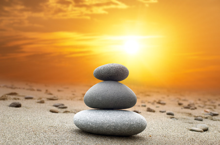 pebbles: Oriental background of stones pyramid at sunset with bright yellow sun on evening sky