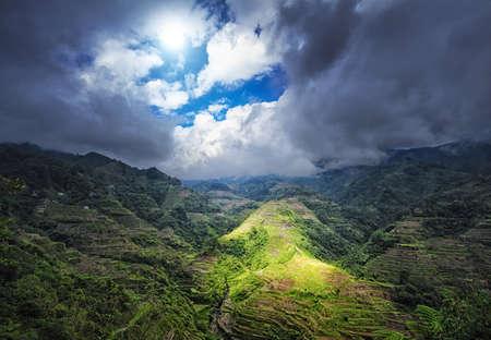 Ray of sun light through clouds under rice terraces in Philippines highlands Stok Fotoğraf