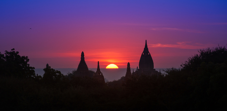 Ancient historical site Bagan in Myanmar at majestic sunset with beautiful sky and sun disk