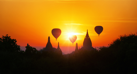 Amazing Myanmar sunset panorama with  temples and hot air balloons flying Stok Fotoğraf