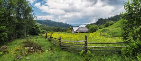 Ukraine rural countryside panorama. Wooden fence and house on Carpathian meadow