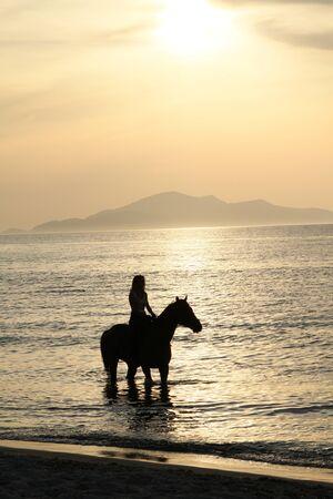 femme et cheval: La femme sur un cheval et un coucher de soleil d'or. Côte de l'île grecque de Kos Banque d'images