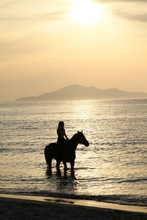 jinete: La mujer en un caballo y una puesta de sol de oro. Costa de la isla griega de Kos Foto de archivo