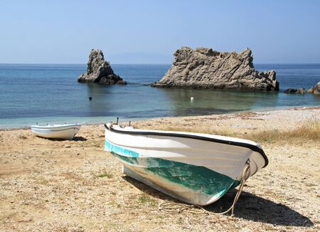 Grands et petits bateaux sur le bord de la mer contre les rochers