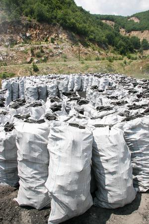 Producción de carbón para braseros y una barbacoa. La tercera etapa - embalaje en bolsas Foto de archivo - 85873605