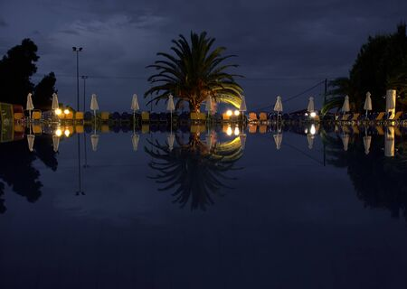 Night pool with reflection of a stormy sky. Lanterns and umbrellas