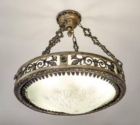 Beautiful bronze chandelier hanging on the ceiling. Bronze chandelier hanging on chains