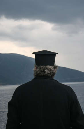Monk looking at Mount Athos. Greece Stock Photo