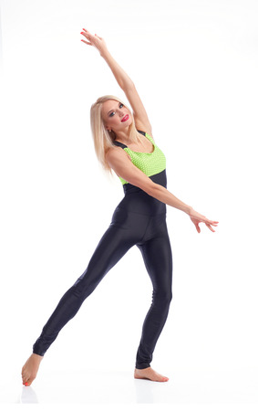 A bit of ballet posing. Studio portrait of a graceful female gymnast posing elegantly smiling to the camera isolated grace fitness training concept