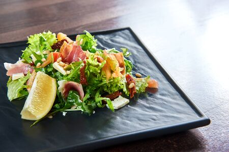 Eating healthy. Closeup of a prosciutto or jamon salad with arugula lemon dorblu cheese and pine nuts copyspace