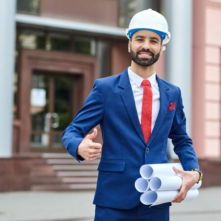 All ideas came together. Portrait of a cheerful male architect wearing hardhat showing thumbs up posing in front of a building  Stock Photo