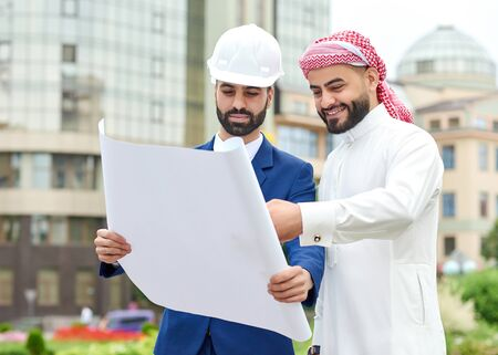 headcloth: I love the project. Cheerful Arab businessman going over some blueprints with his architect Stock Photo