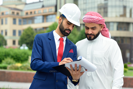 headcloth: Discussing details. Horizontal shot of an outdoor meeting of an engineer and his Saudi client