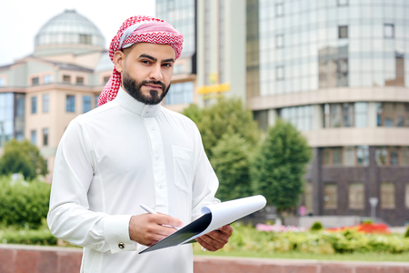 Serio los negocios. Tiro horizontal de un hombre de negocios árabe confía en que mira a la cámara con un portapapeles con documentos Foto de archivo