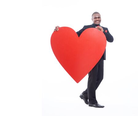 Full lenght portrait of man holding big heart. Stock Photo