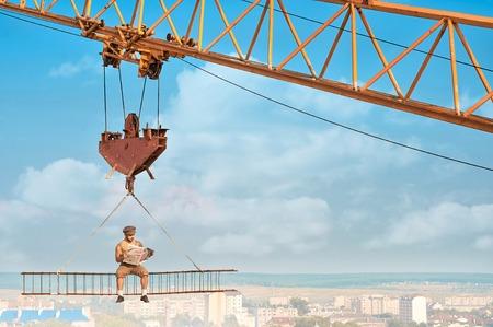 Crane holding iron construction, where sitting builder.