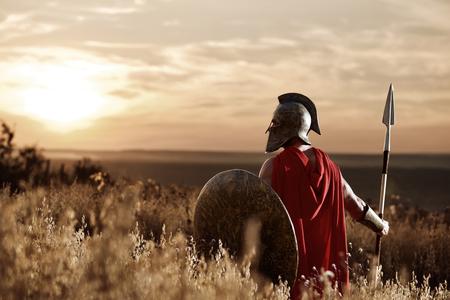 Strijder die ijzeren helm en rode mantel draagt. Stockfoto