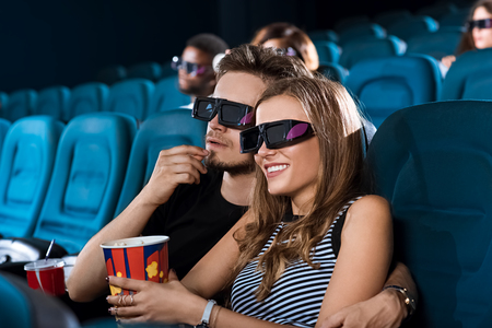 Young happy couple having a date at the cinema