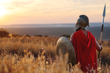 Sterke Spartaanse krijger in de strijd jurk met een schild en een speer Stockfoto - 72741857