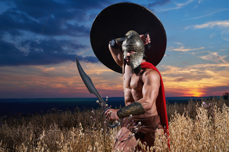 Fearless young Spartan warrior posing in the field Stock Photo
