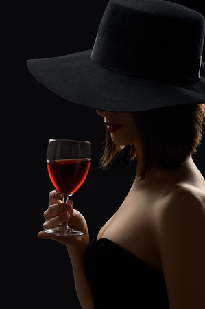 Elegant mysterious woman in a hat holding a glass of red wine on
